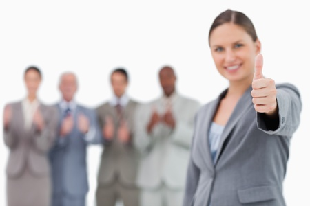 Smiling businesswoman with thumb up and colleagues behind her against a white background photo