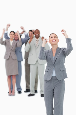 Cheering businesswoman with team behind her against a white background photo