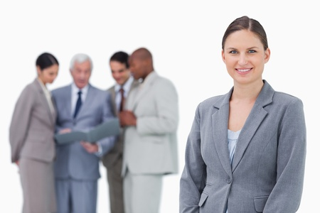 Smiling saleswoman with team behind her against a white background Stock Photo - 13616012