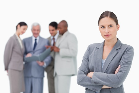 Serious saleswoman with folded arms and team behind her against a white background photo