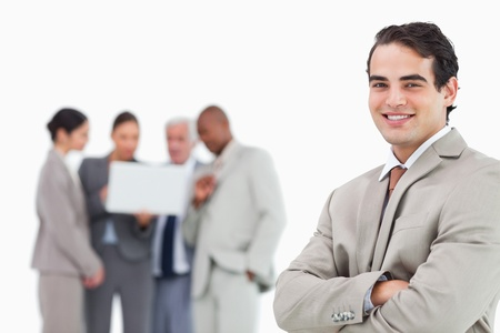 Smiling salesman with arms folded and colleagues behind him against a white background photo