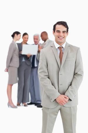 Smiling businessman with team behind him against a white background Stock Photo - 13608970