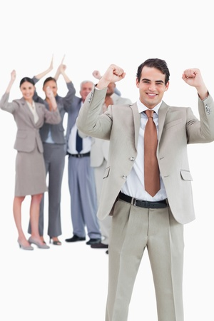 Cheering businessman with team behind him against a white background photo