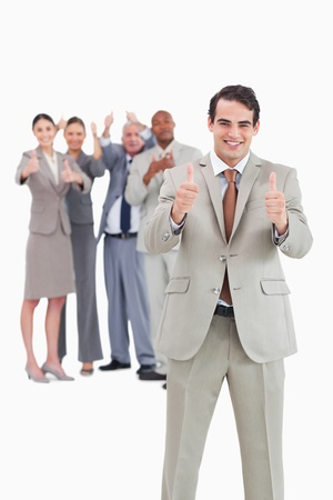 Smiling businessman with team behind him giving thumbs up against a white background photo