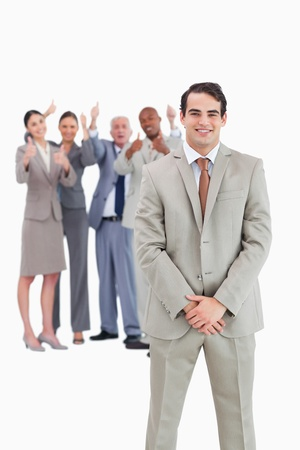 Smiling businessman with cheering team behind him against a white background Stock Photo - 13607362