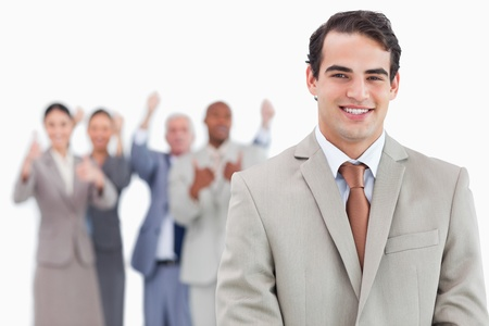 Smiling salesman with cheering team behind him against a white background photo