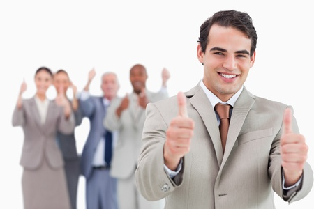 Salesman with team behind him giving thumps up against a white background photo