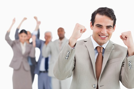 Smiling businessman with team behind him raising fists against a white background photo