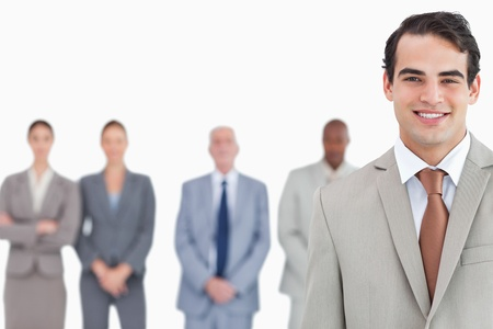 Smiling salesman with colleagues behind him against a white background Stock Photo - 13610310