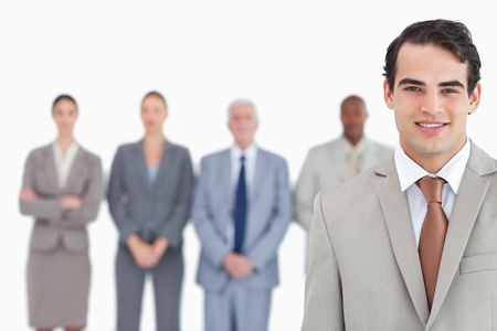 Smiling businessman with his team behind him against a white background Stock Photo - 13615126