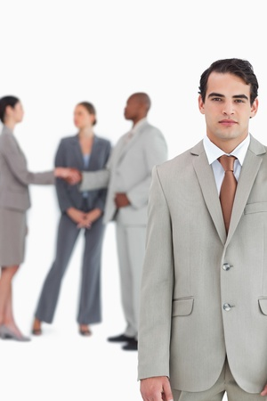 Serious salesman with businesspeople behind him against a white background photo