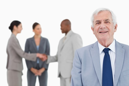 Mature salesman with trading partners behind him against a white background Stock Photo - 13615752