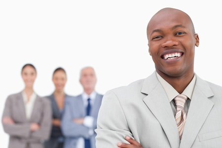Smiling salesman with team behind him against a white background photo