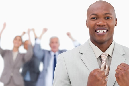 Triumphant businessman with cheering team behind him against a white background photo