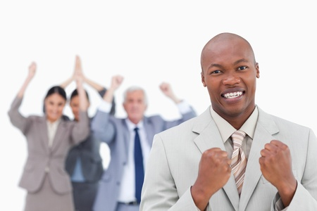 Successful businessman with cheering team behind him against a white background photo