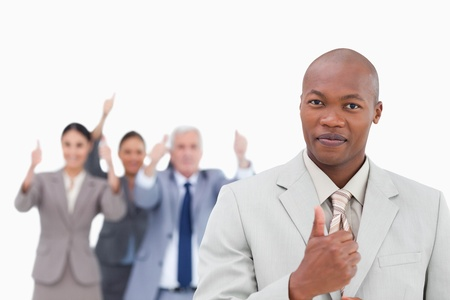 Businessman with cheering team behind him giving thumb up against a white background photo