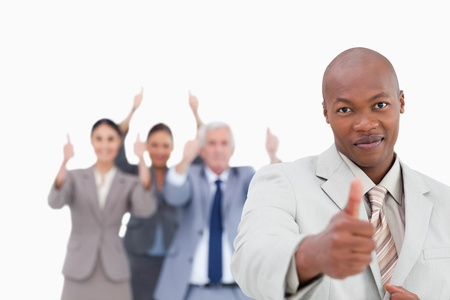 Businessman with cheering team behind him giving approval against a white background photo