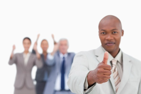 Salesman with team behind him giving approval against a white background photo