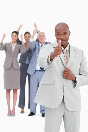 Tradesman with team behind him giving thumb up against a white background photo