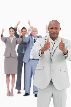 Tradesman with cheering team behind him giving thumbs up against a white background photo