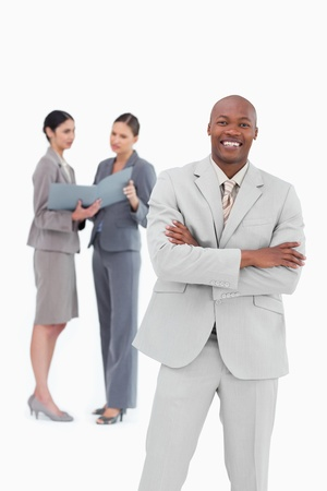 Smiling businessman with co-workers behind him against a white background photo