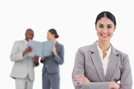 Smiling saleswoman with arms crossed and colleagues behind her against a white background photo