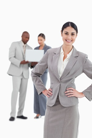 Smiling businesswoman with hands on her hip and colleagues behind her against a white background photo