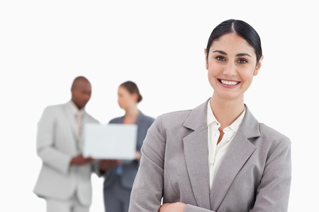 Smiling businesswoman with talking colleagues behind her against a white background photo