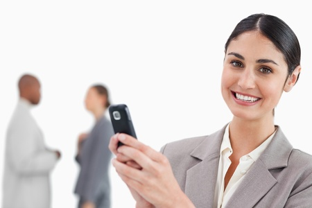 Smiling saleswoman holding cellphone with colleagues behind her against a white background photo