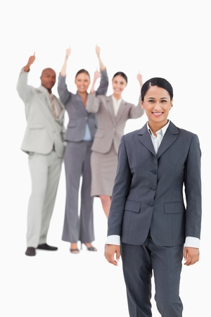 Smiling saleswoman with cheering team behind her against a white background photo