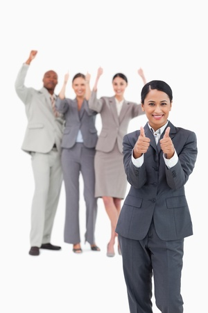 Saleswoman with cheering team behind her giving thumbs up against a white background photo