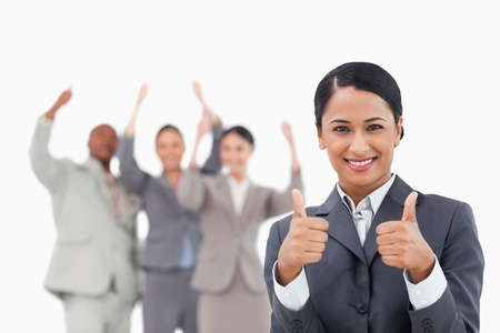 Saleswoman with cheering team behind her giving approval against a white background photo