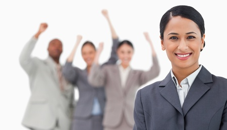 Smiling saleswoman with cheering colleagues behind her against a white background photo