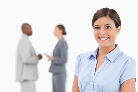 Smiling businesswoman with talking associates behind her against a white background photo