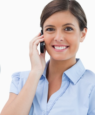 Smiling businesswoman with cellphone against a white background photo