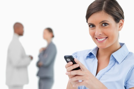 Smiling saleswoman holding mobile phone with colleagues behind her against a white background photo