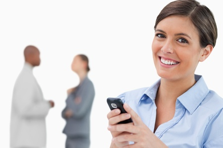 Smiling saleswoman with mobile phone and associates behind her against a white background photo