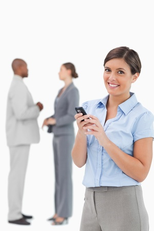 Smiling tradeswoman with cellphone and associates behind her against a white background Stock Photo - 13607364