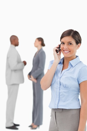 Smiling saleswoman on the phone with associates behind her against a white background photo