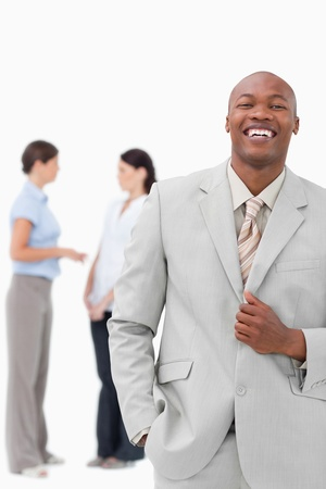Laughing salesman with colleagues behind him against a white background photo