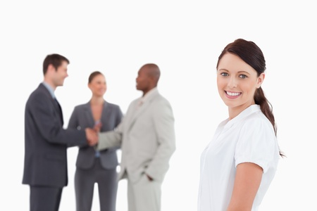 Smiling saleswoman with three colleagues behind her against a white background photo