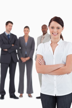 Businesswoman with arms folded and three colleagues behind her against a white background Stock Photo - 13608606