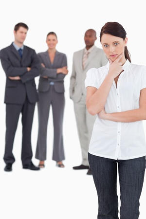 thinkers: Thinking businesswoman with three colleagues behind her against a white background Stock Photo