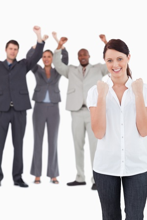 Successful businesswoman with cheering colleagues behind her against a white background photo