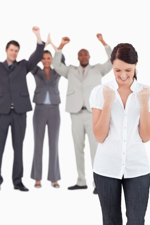 Triumphant businesswoman with cheering colleagues behind her against a white background photo