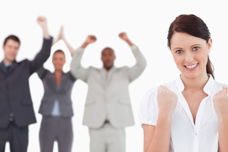 Victorious businesswoman with cheering team behind her against a white background photo