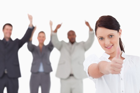 Businesswoman with cheering colleagues behind her giving thumb up against a white background photo