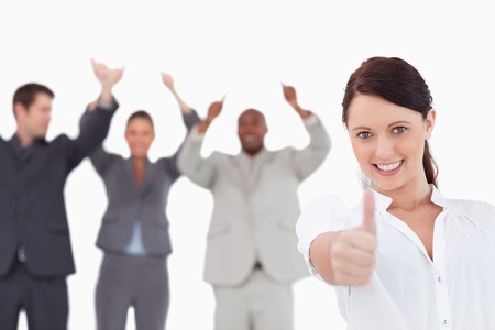 Saleswoman with cheering colleagues giving thumb up against a white background photo
