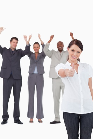 Businesswoman with cheering colleagues behind her giving approval against a white background photo