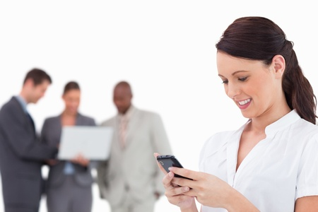 Businesswoman writing text message with colleagues behind her against a white background photo
